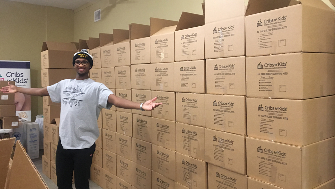 Bryant student with boxes packed as part of service project at Cribs for Kids