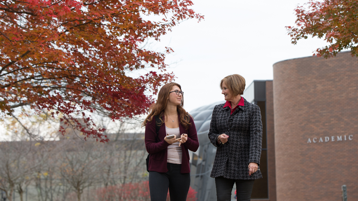 Professor Coakley and student walk on campus