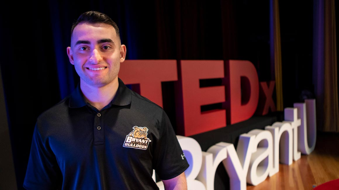 Michael Biskupic in front of TEDxBryantU sign
