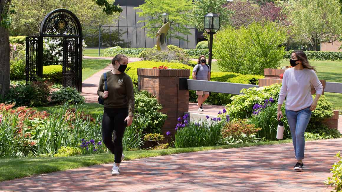 Two students wear masks and walk on campus