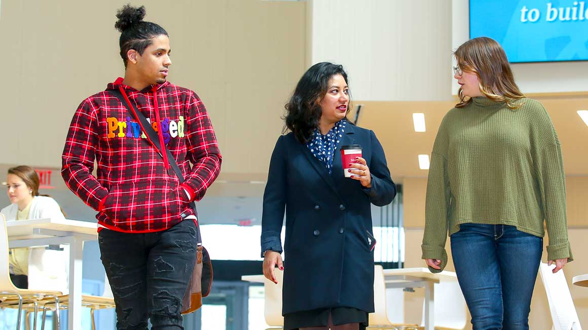Professor Diya Das walks with two Bryant students