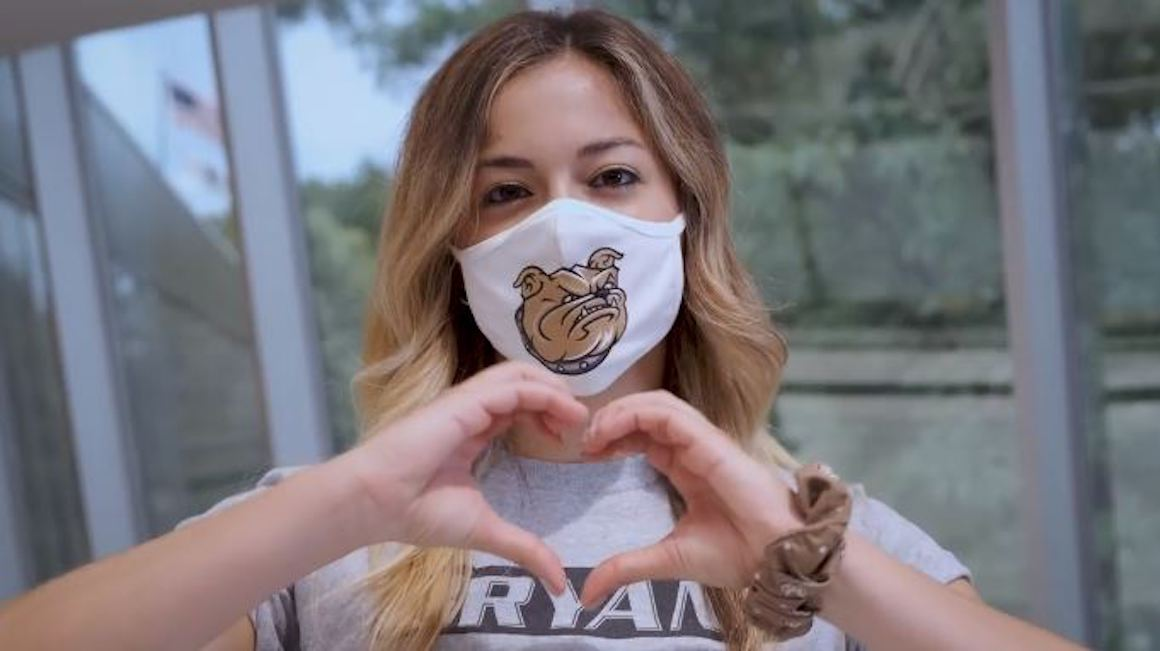 student wearing mask makes a heart shape with her hands