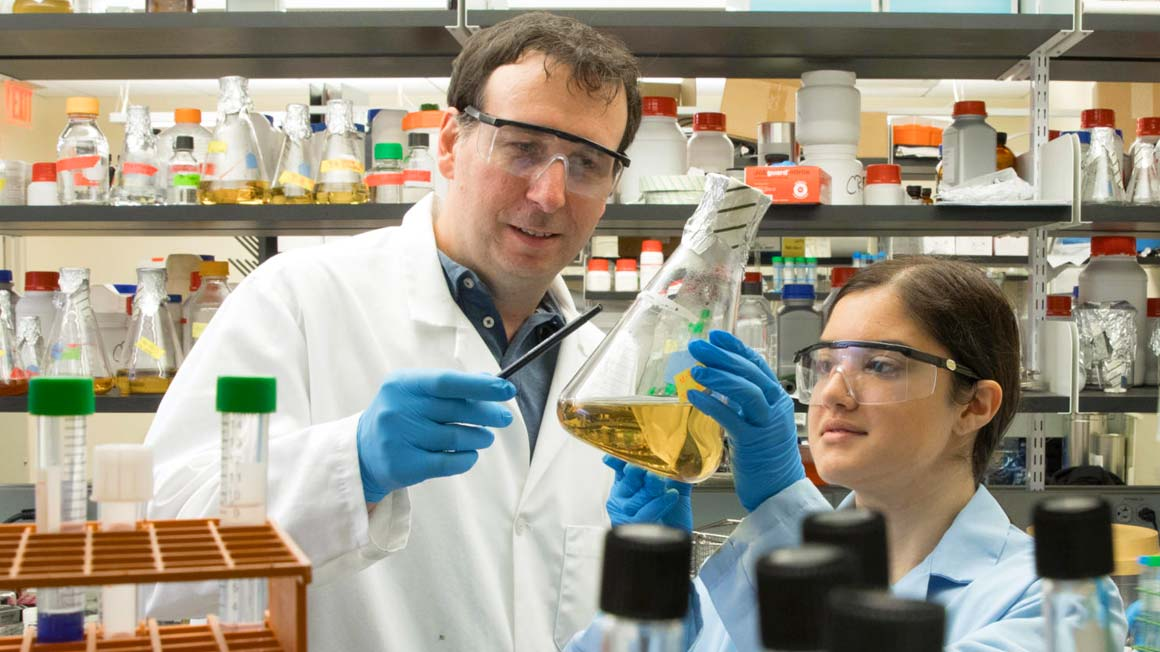 Professor Chris Reid works with a student in a science lab.