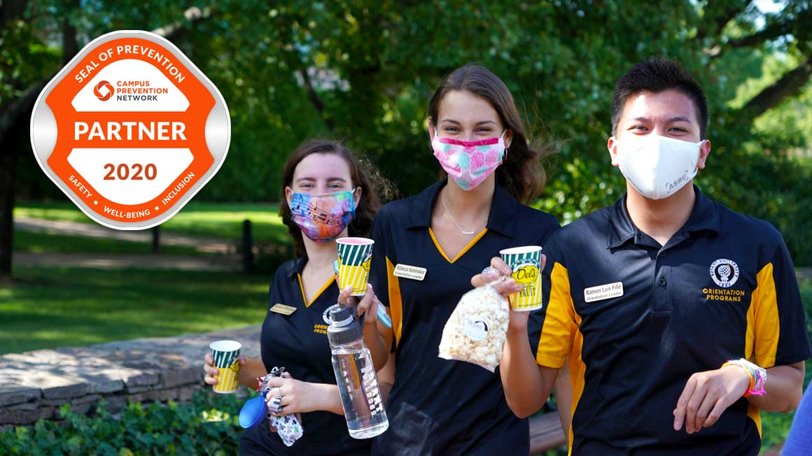 three students wearing masks and holding healthy beverages